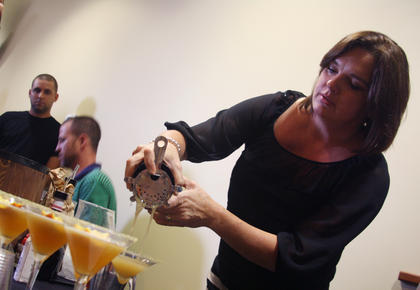 "Sandy Holt, a bartender at Bourbon City Bistro, focuses as she pours the restaurant's mixed drink, ""Blurred Lines,"" before Wednesday's Mixed Drink Challenge."