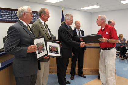 Nelson County track and cross-country coach Dan Bradley, right, presented a token of thanks to the Nelson County School Board for the completion of the new track facilities at the high school.