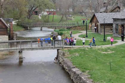 Teachers escort elemenary school students across the bridge near the mill at Old Bardstown Village Friday.