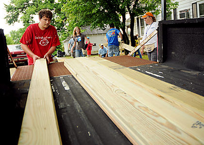 Zachary Oakes, Hopkinsville, removes a plank from a truck for a construction project at a home in Bloomfield.