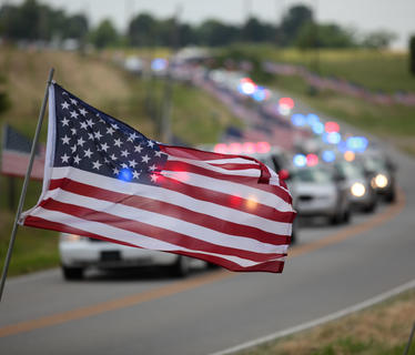 An American flag flies in front of the funeral procession for Jason Ellis, on Thursday. The procession of several hundred vehicles stretched for miles.