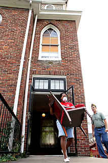 Robin Brock, Bardstown, carries a chair out of the 199-year-old former First Baptist Church on North Second Street. About 50 people turned out Saturday morning to kick off its renovation into the Reverend Roy Henry Educational Center. Brock is a member of First Baptist.