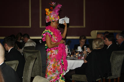 Angela Nance, dressed as a Copacabana girl, hold up clues for sale during the trivia night portion.