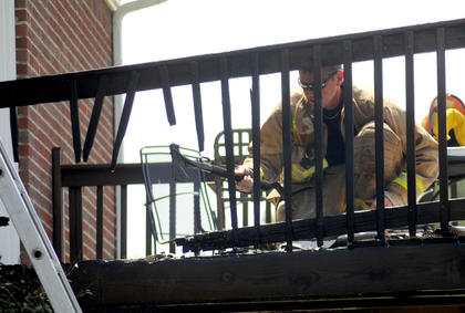 First Assistant Chief Marlin Howard, Bardstown-Nelson County Volunteer Fire Department, clears the charred remains of a deck on Topeka Lane in Nelson County Thursday. An eyewitness said the fire was started by a cigarette butt.