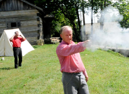 Marvin Crone, Sellersburg, fires a black powder colt pistol at the Old Bardstown Village Saturday.