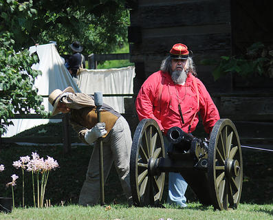 Larry Bruner prepares to fire a 6 pound mountain Howitzer cannon at Old Bardstown Village Saturday. Brigette Fasciotto, Louisville stands nearby, bracing for the shot to fire. Bruner said the cannon is the only of its type known to exist in Kentucky. Campers dressed in Civil War era clothing spent the weekend sleeping in tents and recreating battles at the Old Bardstown Village.