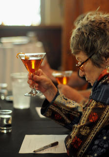 Judge Joy Perrine closely examines a drink at the Mixed Drink Challenge at the Chapel at Spalding Hall Wednesday.