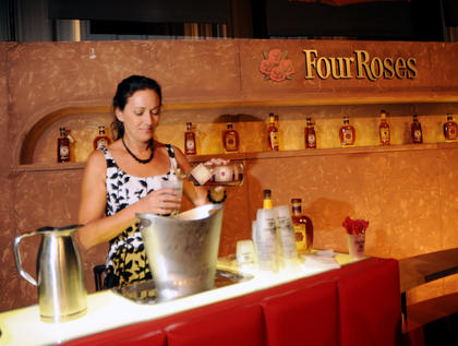 Mary Drummer pours a drink at the Four Roses booth at the Kentucky Bourbon All-Star Sampler at the Guthrie Opportunity Center Wednesday.