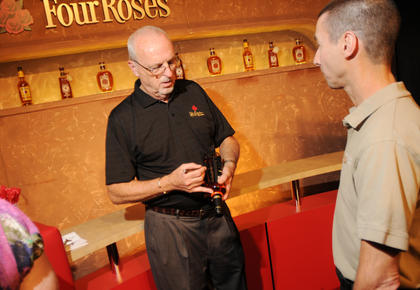 Jim Rutledge, Master Distiller at Four Roses Distillery, signs a bottle of Four Roses bourbon for Sonny Hopper, Bardstown. Hopper bought the bottle, which is an export-only bottle, in Japan.