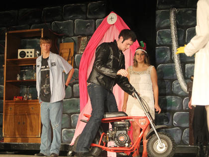 "Eddie, played by Michael Constantine, arrives on his motorbike during a performance of ""The Rocky Horror Show."" Behind him are two of the Phantoms, played by William Hopkins and Shelby Gelhaus."