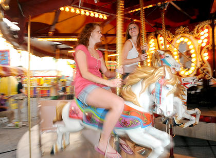 Sierra Bellah and Ashley Seaman, Bardstown, ride the merry-go-round at the Nelson County Fair Monday.