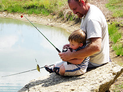 Braden House,2, fishes with his dad, Daryl, at the home of Braden's grandfather, Larry Dones. It was Braden's first fishing trip and he caught his first fish