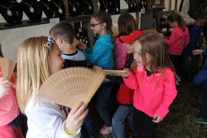 Emma Legel, left, and Madeline Wheeler fan each other while visiting a merchant's tent with other Mount Washington Elementary students Friday at Bardstown Colonial Days.