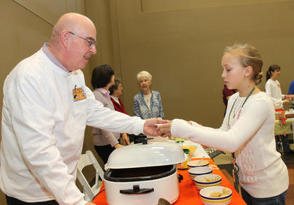 Greg Blevins serves some chili to Maggie Mattingly at the St. Vincent de Paul benefit, Souper Bowl of Caring, sponsored by the St. Joseph teen group, W.O.W.