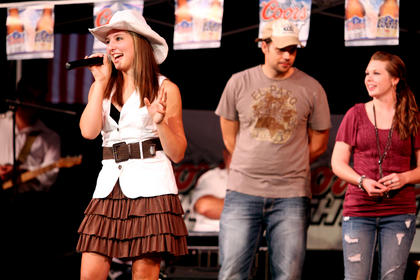 Makayla Richardson sings after winning the competition. Behind her are third-place winner Jason Eustice, Shelbyville, and second-place winner Krista Lynn Brady, New Haven.