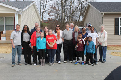 Habitat for Humanity's newest homeowners, Sharon Bolin and Kimberly Phillips, and their children pose with volunteers and board members for a team photo.