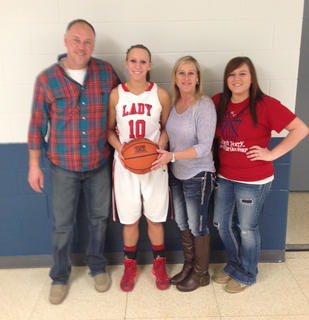 Nelson County junior Caitlin Hagan (second from left) joined the 1,000-point club during the Cardinals' win Tuesday over Taylor County. Hagan is pictured with her father, Paul, her mother, Christy, and sister, Amber.