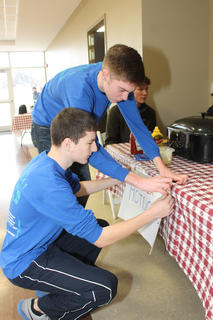 "Bethlehem High School students Jonathan Smith, kneeling, and Thomas Rogers affix a ""Super Hot Dogs"" sign to their table at the Souper Bowl Saturday at St. Joseph Hall Saturday. St. Gregory Parish provided the wieners and fixings."