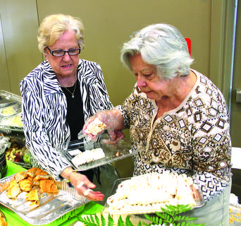 Darlene Crume and Juanita Hobbs prepare to serve ham-and-cream cheese wraps for the Bloomfield Baptist Church at the Habitat Tasting Bash.