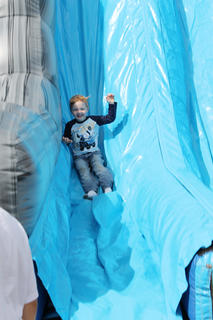 Conner Mercer, 4, of Cox's Creek smiles as he goes slipping down a giant inflatable slide at Flaget Memorial Hospital.