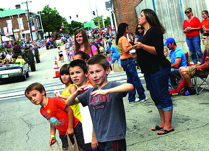 Children eagerly await candy thrown from cars and floats in the parade.