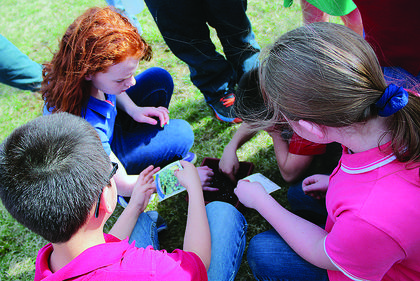 Kids help plant cilantro and basil outside of a nature trail Monday.