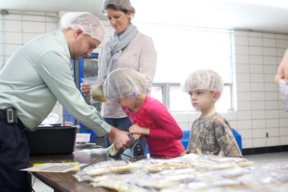 Sarah Rouse, 9, seals a bag of raw ingredients that will make six servings of rice and soy casserole Monday while Tim Travis holds the bag steady. Her brother Mikey Rouse, 6, stands ready to take the bag from her while her mother, Sarah Rouse, prepares another bag to be sealed.