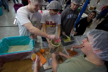 Bethlehem High School students measure rice and soy to pack into a bag as part of the  Interact Club's service project Monday to benefit Kids Against Hunger.
