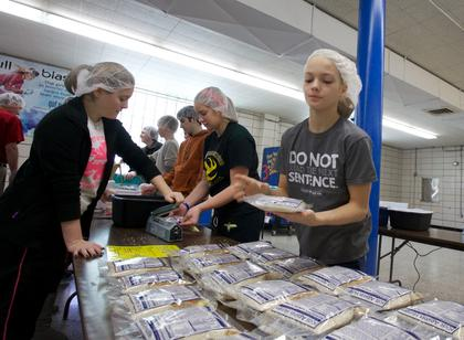 Jeanie Downs piles bags of raw ingredients packed by volunteers at Bethlehem High School Monday as part of the school's Interact Club's day of service to benefit Kids Against Hunger.