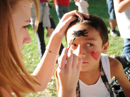 Kelly Feldman paints a spider on Josiah Jones, 7, Bardstown at Kid's Day Thursday. Kid's Day is sponsored by the Bardstown Rotary Club.