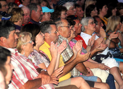 Audience members clap in rhythm during a performance by Lee Greenwood at the J. Dan Talbott Ampiteatre Saturday.