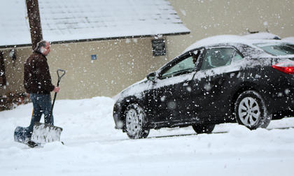 Individuals reach out to help one another dig out cars in town Thursday morning.