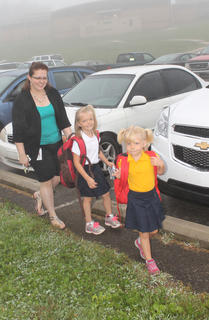 Lana Flanagan, 5, right, and her sister, Ryann Flanagan, 7, show off their matching pink backpacks on the first day of classes at Bardstown Primary School, while their mother, Dawn Flanagan, watches them, smiling.