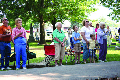 Locals show respect as the National Anthem plays at the Memorial Day ceremony at Bardstown Cemetery.