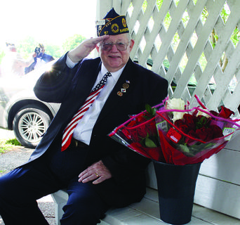 Russ Marlowe poses next to roses that were passed out to widows at the Memorial Day ceremony at Bardstown Cemetery Monday. The roses were donated by Andy Logston, a manager at Walmart, who has been donating the flowers for the past 15 years.