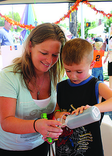 A mom helps her son make a colorful decoration by filling a plastic cross with sand of different hues.