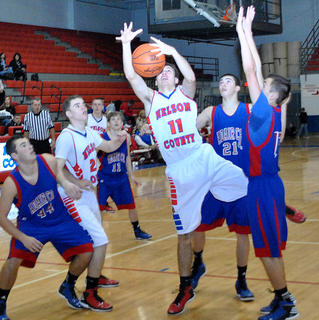 Nelson County&#039;s Joseph Cesare snares a rebound against Adair County during the Cardinal Classic over the holidays.