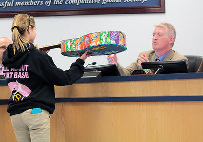 A Bloomfield Middle School student shows Nelson County Board of Education Chairman Damon Jackey a guitar art piece she made for Beta Club.