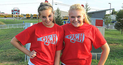 Abby Pettit and Kaitlyn Cecil, cheerleaders at OKHMS, show their school spirit.