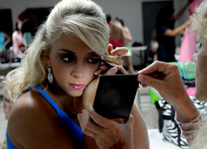 Lyndsey Cook, Danville, applies make-up in a mirror backstage before the Miss Nelson County Fair Pageant.
