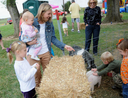 Tate Blincoe, Layne Blincoe and their mother, Leslie Blincoe look at the animals in the petting zoo at Watson's Pumpkin Festival Sunday.