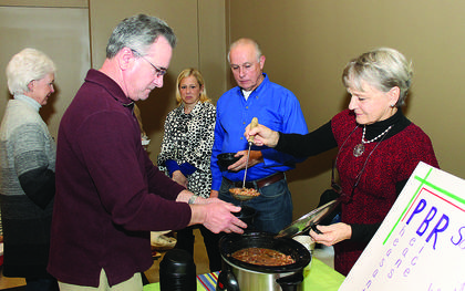 Lynne Bowling serves Sidney Hagan at the PBR Soup table at the St. Joseph Catholic Church's Souper Bowl of Caring. The PBR stands for pheasant, beans and rice. Money from donations at the event goes to benefit the St. Vincent de Paul Society.