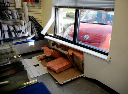 Tristan Newton's Volkswagon Beetle rammed through the front of the United States Post Office at 510 West Stephen Foster Wednesday. Newton said her vehicle suddenly accelerated. No injuries were reported. The car caused structural damage to the building and dislocated a window from its frame. Sales associates Natalie Cole and Diana Leachman were inside the post office when the car crashed into the building.