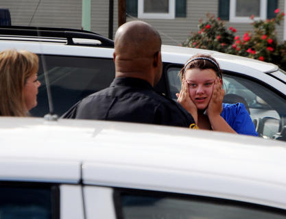 Postmaster Cindy Beasley, Bardstown Police Major Ray Lewis talk to Tristan Newton after Newton's Volkswagon Beetle rammed through the front of the United States Post Office at 510 West Stephen Foster Wednesday. Newton said her vehicle suddenly accelerated. No injuries were reported. The car caused structural damage to the building and dislocated a window from its frame. Sales associates Natalie Cole and Diana Leachman were inside the post office when the car crashed into the building.