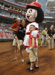 Amy Ellis, wife of slain Bardstown police officer Jason Ellis along with her sons Hunter, 7, left and Parker, 6 gets a hug from Cincinnati Reds mascot Rosie Red prior to their game against the Pittsburgh Pirates at Great American Ball Park. The Enquirer/Jeff Swinger