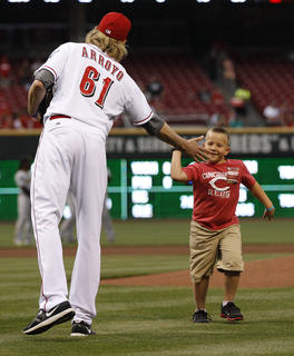 Cincinnati Reds starting pitcher Bronson Arroyo (61) slaps five with Parker Ellis, 6 son of slain Bardstown police officer Jason Ellis after throwing out the ceremonial first pitch before their game against the Pittsburgh Pirates at Great American Ball Park. The Enquirer/Jeff Swinger