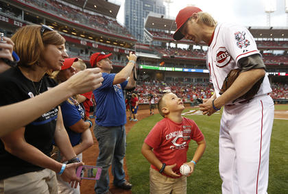Cincinnati Reds starting pitcher Bronson Arroyo (61) signs an autograph for Parker Ellis, 6 son of slain Bardstown police officer Jason Ellis after throwing out the ceremonial first pitch before their game against the Pittsburgh Pirates at Great American Ball Park. His mother Amy Ellis watched, left.  The Enquirer/Jeff Swinger