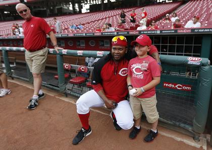 Cincinnati Reds starting pitcher Johnny Cueto (47) poses for a photo with Parker Ellis, 6 son of slain Bardstown police officer Jason Ellis while he was a special guest for the Reds prior to their game against the Pittsburgh Pirates at Great American Ball Park. The Enquirer/Jeff Swinger