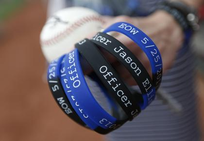 Bracelets for slain Bardstown police officer Jason Ellis were being handed out at the Cincinnati Reds game by his son Parker Ellis, 6 while he was a special guest for the Reds prior to their game against the Pittsburgh Pirates at Great American Ball Park. The Enquirer/Jeff Swinger