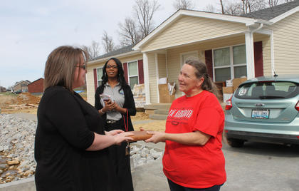 Kristen Ross presents Sharon Bolin her Bible at the dedication ceremony for her Habitat house at 115 McGowan Ave. Sunday afternoon. Behind them is Lucretia Starnes, president of My New Kentucky Home Habitat for Humanity.